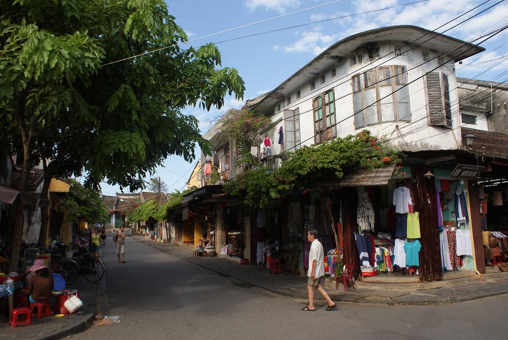 Dans une rue de Hoi An au Vietnam entre végétation, petits commerces et maisons coloniales.