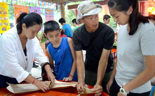 吳永斌(右二)教導民眾利用檳榔葉鞘製作成碗。(攝影:謝宗璋)