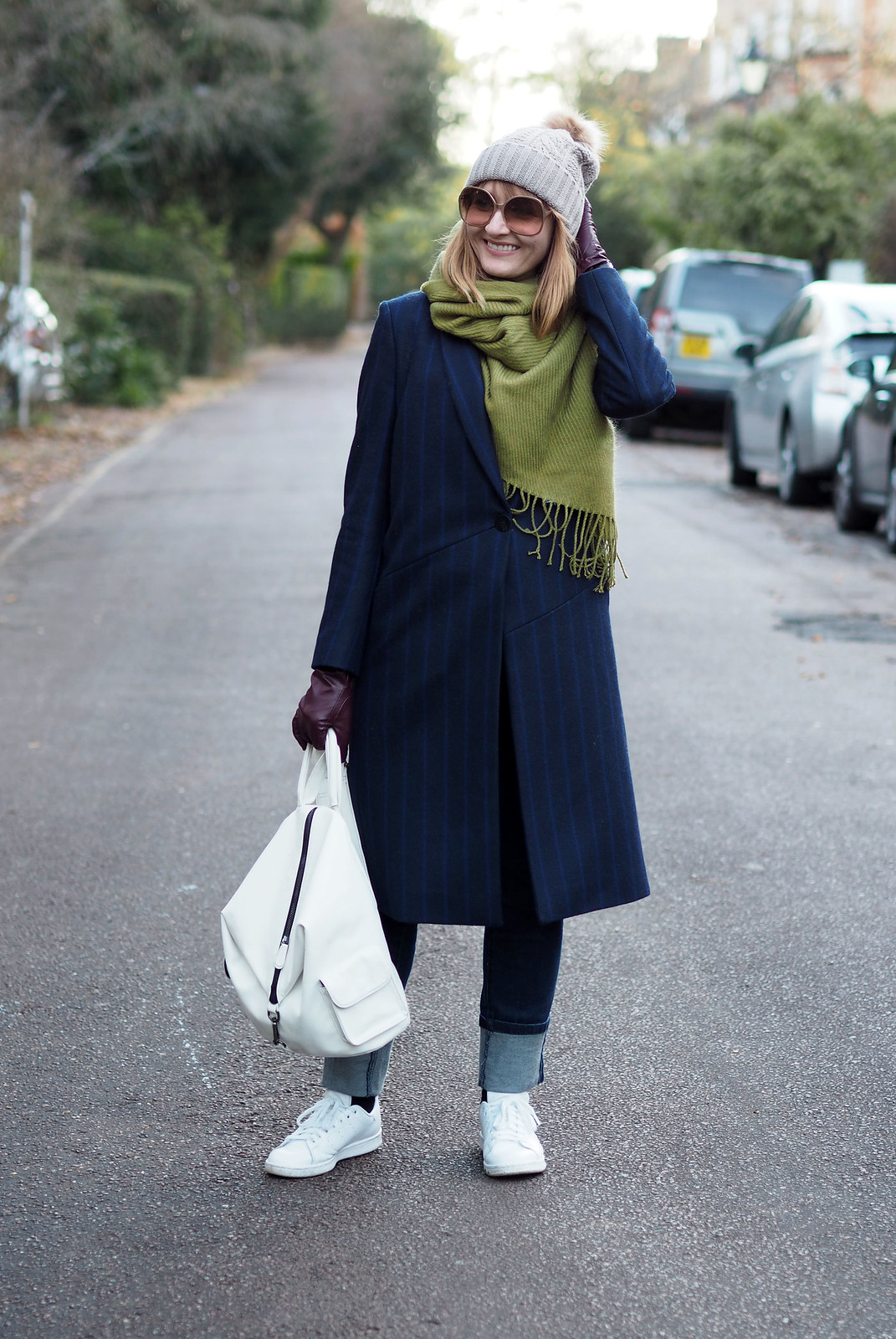 Smart cold weather layered outfit  navy pinstripe wool coat  moss green wool scarf  bobble hat  white backpack and Adidas Stan Smiths  deep hem straight leg jeans | Not Dressed As Lamb, over 40 style