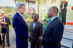 U.S. Secretary of State John Kerry speaks with Haitian social media leaders Carel Pedre and John Fritz Moreau in Port-au-Prince, Haiti, on October 6, 2015. [State Department photo/ Public Domain]