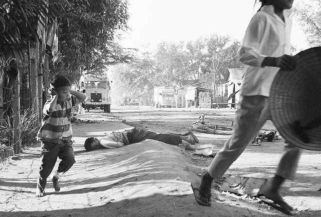 DA NANG 1968 - A dead civilian lies nearby as a young Vietnamese boy shields his ears from gunfire blasts and runs for cover on a Da Nang street on January 31, 1968