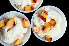 Three vanilla ice-cream with peach isolated on bla…
