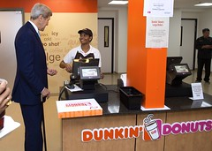 U.S. Secretary of State John Kerry buys a dozen doughnuts at the newly opened Massachusetts-based Dunkin' Donuts franchise in the State Department cafeteria in Washington, D.C., on September 4, 2015. [State Department photo/ Public Domain]