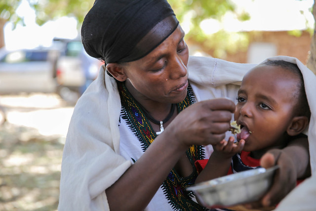 Asmera Bere feeds her son, Amanuel Shibabaw, feeds to her child a nutritious porridge made from locally available products, at the health post as a demonstration to cook at home