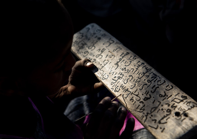 Afar tribe girl writing on a wood board in a Coranic school, Afambo, Ethiopia