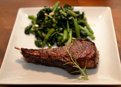Lamb chops with a side of sautéed kale, string be…