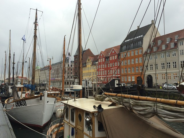 Nyhavn canal boats docked along street with buildings and fog Copenhagen