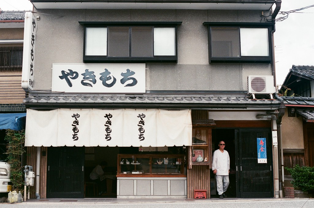 北野天滿宮 京都 Kyoto 2015/09/26 我愛這樣的店家風格,剛好老闆要走出來。  那時候蹲在馬路上拍照在準備按下快門的時候看到老闆好像要走出來,我就等他走到我想要的位置再按下快門。  Nikon FM2 Nikon AI Nikkor 50mm f/1.4S AGFA VISTAPlus ISO400 0952-0027 Photo by Toomore