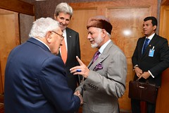 U.S. Secretary of State John Kerry watches as former U.S. Secretary of State Henry Kissinger greets Omani Foreign Minister Yusuf bin Alawi before Secretary Kerry's bilateral meeting with the Omani Foreign Minister on the sidelines of the 70th Regular Session of the UN General Assembly in New York, New York, on October 2, 2015. [State Department photo/ Public Domain]