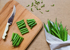 Sliced green beans  and a bunch of green beans on…
