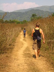 a dirt path through a meadow with two individuals walking, one following the other