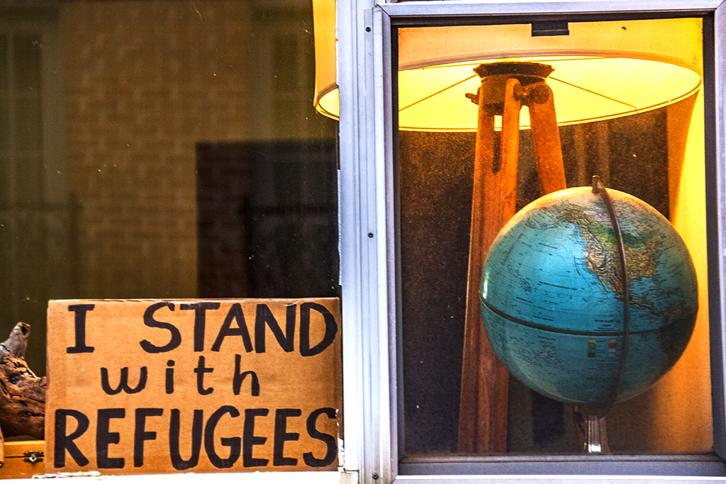 I STAND WITH REFUGEES sign and globe in window--Bella Vista