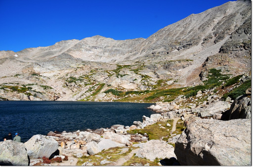 A social trail rounds the north shore of Blue Lake before fading into the landscape, background is Paiute Peak