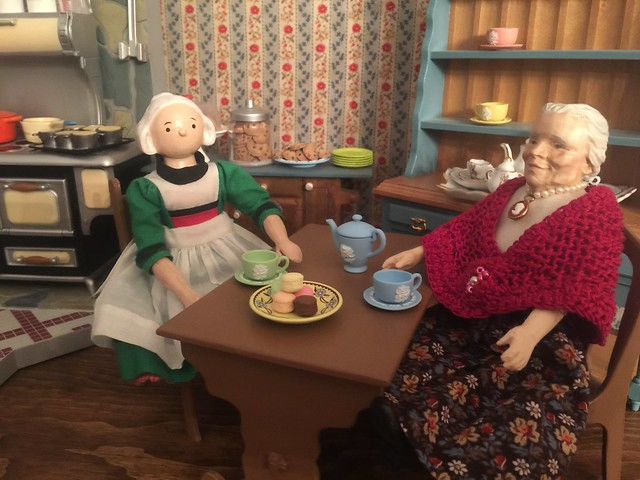 Becassine and Grandma chat while enjoying tea and some sweet treats.
