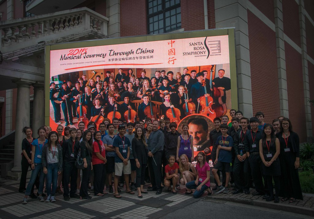 Santa Rosa Symphony Youth Orchestra in front of the giant billboard advertising their concert in the He Luting Concert Hall of the Shanghai Conservatory of Music
