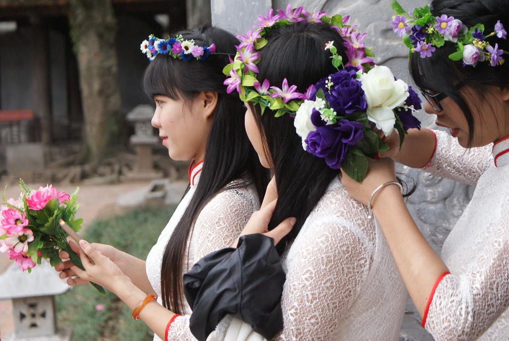 Etudiantes vietnamiennes au temple de la littérature ajustant leur couronnes de fleurs avant selfie.