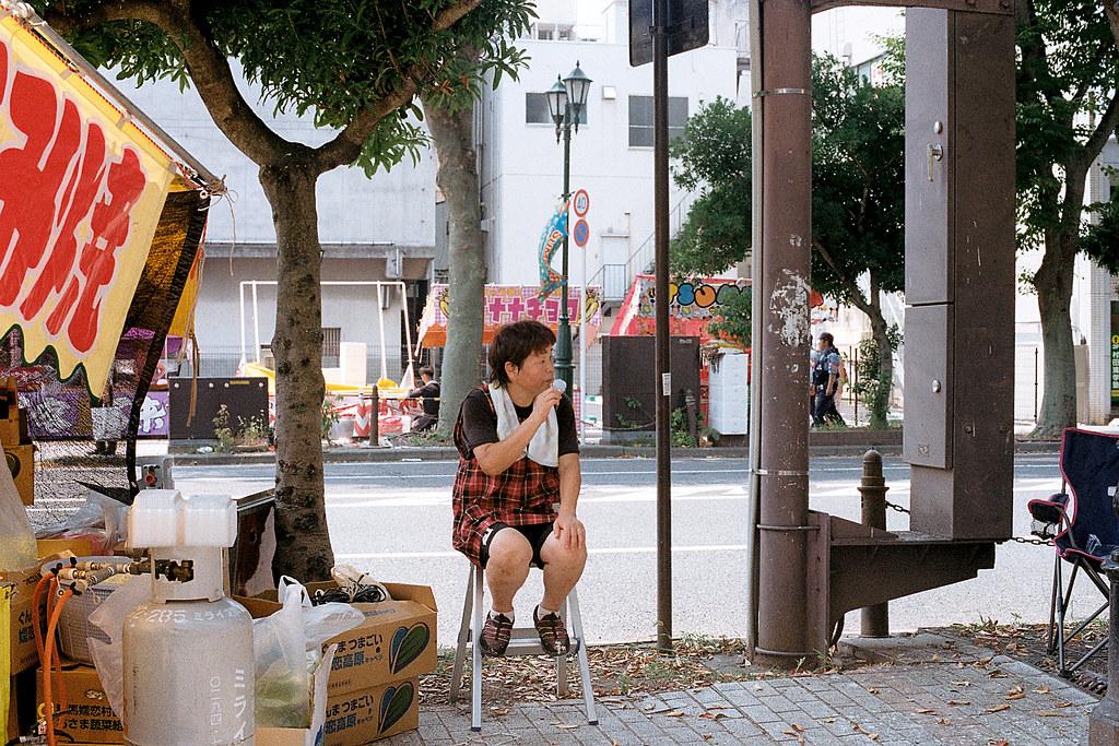 """七夕祭 Iwaki (いわき市 Iwaki-shi), Fukushima 2015/08/06 在日本那時候各地方都很熱,老闆娘趁著沒人空檔的時候吃冰棒,看的我也很想吃。  Nikon FM2 / 50mm Kodak ColorPlus ISO200  <a href=""""http://blog.toomore.net/2015/08/blog-post.html"""" rel=""""noreferrer nofollow"""">blog.toomore.net/2015/08/blog-post.html</a> Photo by Toomore"""