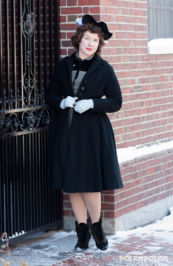 1950s vintage winter outfit featuring a black hat with blue feathers, black and white wool and velvet dress, black princess coat, overshoes, and blue gloves