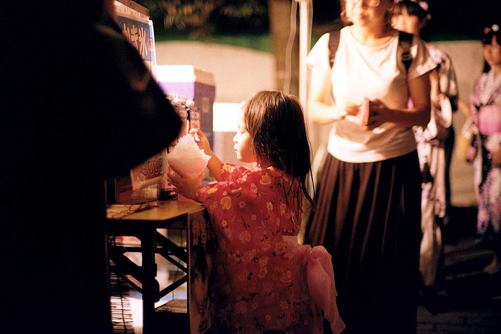 """七夕祭 仙台 Sendai 2015/08/07 看著眼前桌上的那碗冰的小女孩。  Nikon FM2 / 50mm Kodak ColorPlus ISO200  <a href=""""http://blog.toomore.net/2015/08/blog-post.html"""" rel=""""noreferrer nofollow"""">blog.toomore.net/2015/08/blog-post.html</a> Photo by Toomore"""