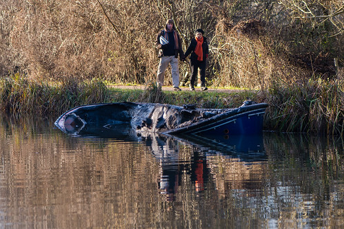 Partially submerged canal boat after fire with onlookers