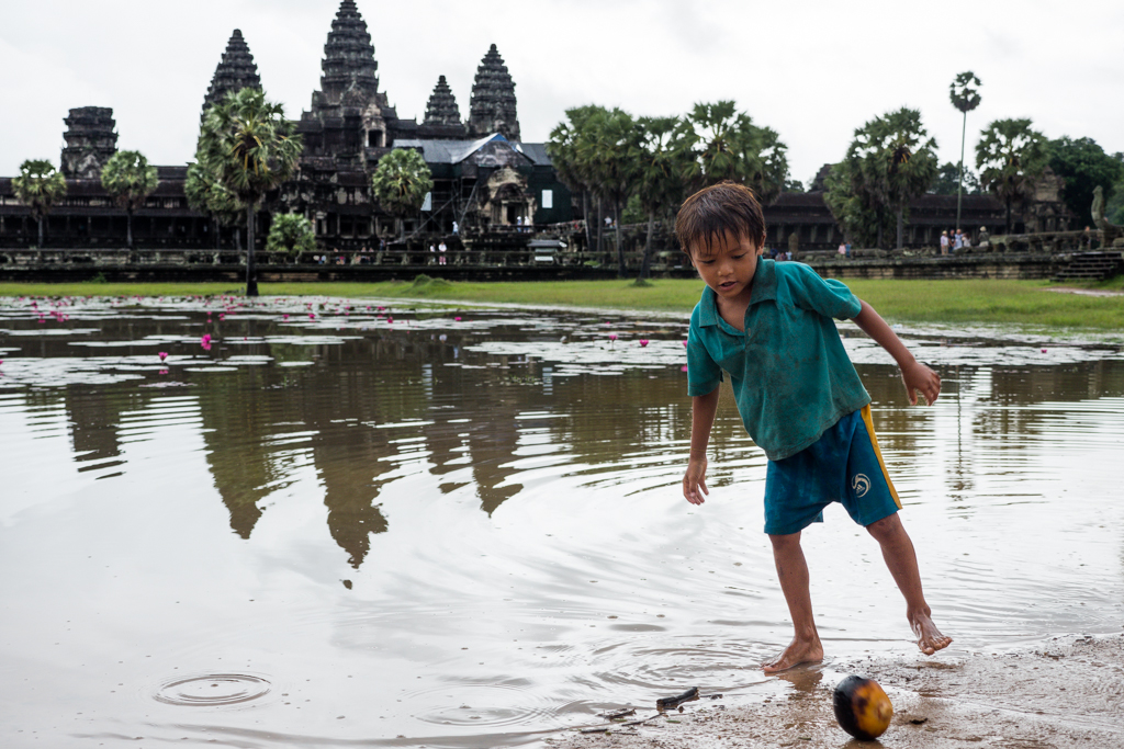 Angkor Wat Temple entrance boy plays foot ball with coconut in Siem Reap, Cambodia