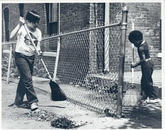 Boys with brooms participating in neighborhood cleanup