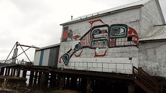 Totemic style mural of a salmon, hand, eyes, fins, clapboard, cannery and processing plant, crab, red turquoise black, paint, wood, peeling, walkway, dock,  South Bend, Washington, USA