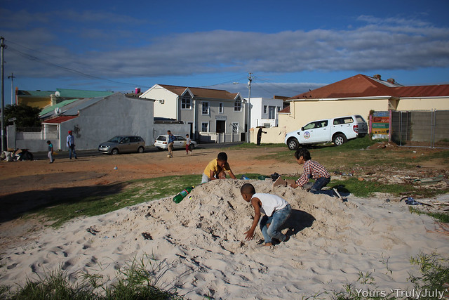 The local kids are playing in the sand we got delivered for building our house.