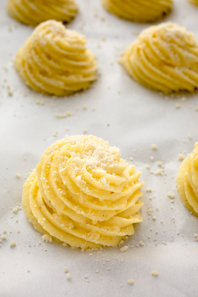 piped parmesan duchess potatoes on baking sheet