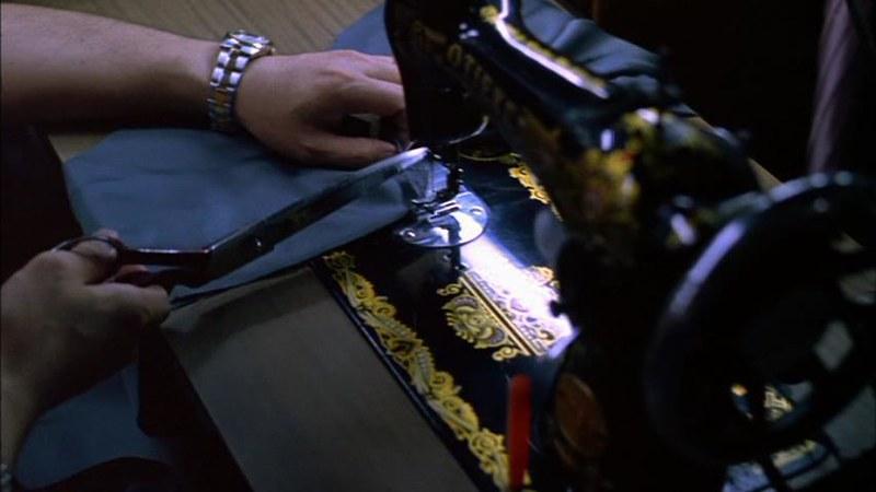 麻薬を隠すためにミシンを使ってズボンに細工をしている場面。