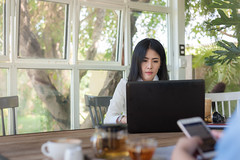 Young Asian woman working with laptop in coffee shop