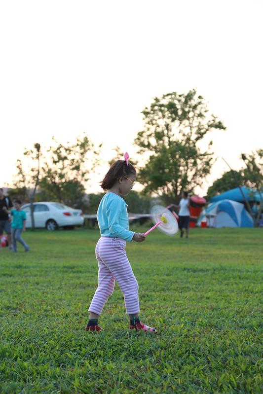 在草地上吹風車的寶妹
