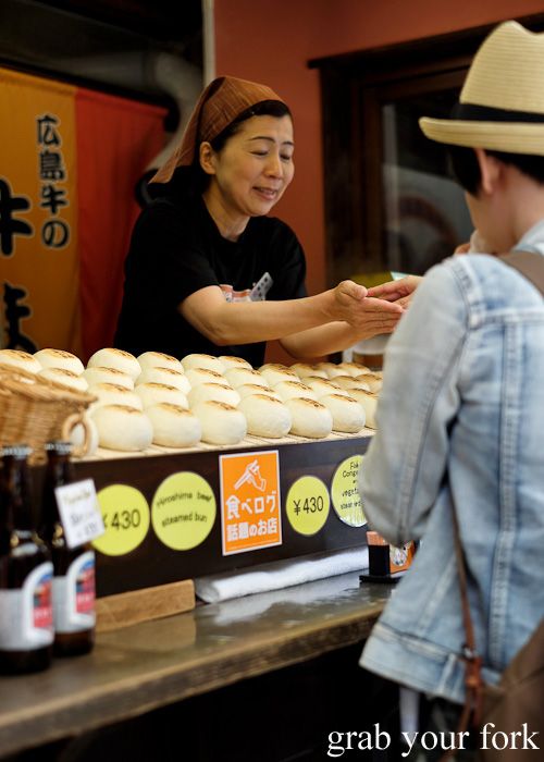 Buying steamed buns with anago conger eel on Miyajima Island