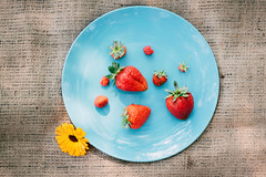 Ripe red strawberries, raspberries and a yellow fl…
