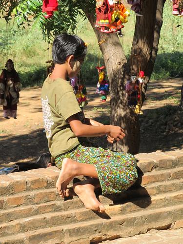 Bagan: jeune fille faisant un bracelet au temple Dhammayangyi Patho