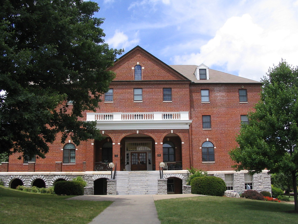 a red brick building with white stone foundation and staircase, with arches and windows
