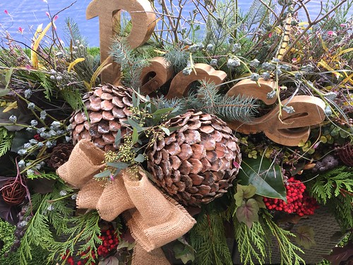 outdoor evergreen christmas arrangement with wood cut-out of the word peace