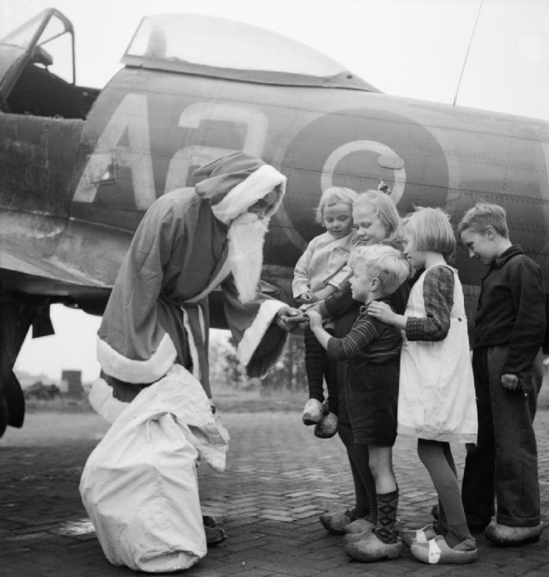 Leading Aircraftman Fred Fazan dressed as Santa Claus hands out presents to Dutch children at No. 122 Wing's airfield at Volkel, Holland, 13 December 1944
