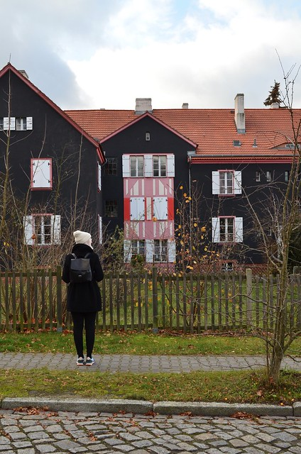 UNESCO World Heritage Site Berlin Modernism Housing Estates Gartenstadt Falkenberg Garden City Tuschkastensiedlung looking at large black house with graphic accents wearing CRU London Gordon backpack