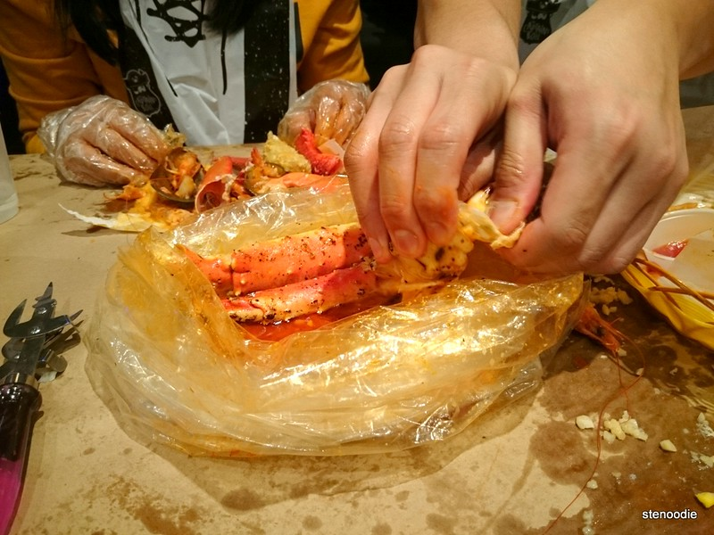 using hands to open seafood in bag
