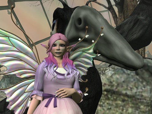 Image Description: Woman in a pink and purple dress with pink and purple hair standing in front of a giant crow.