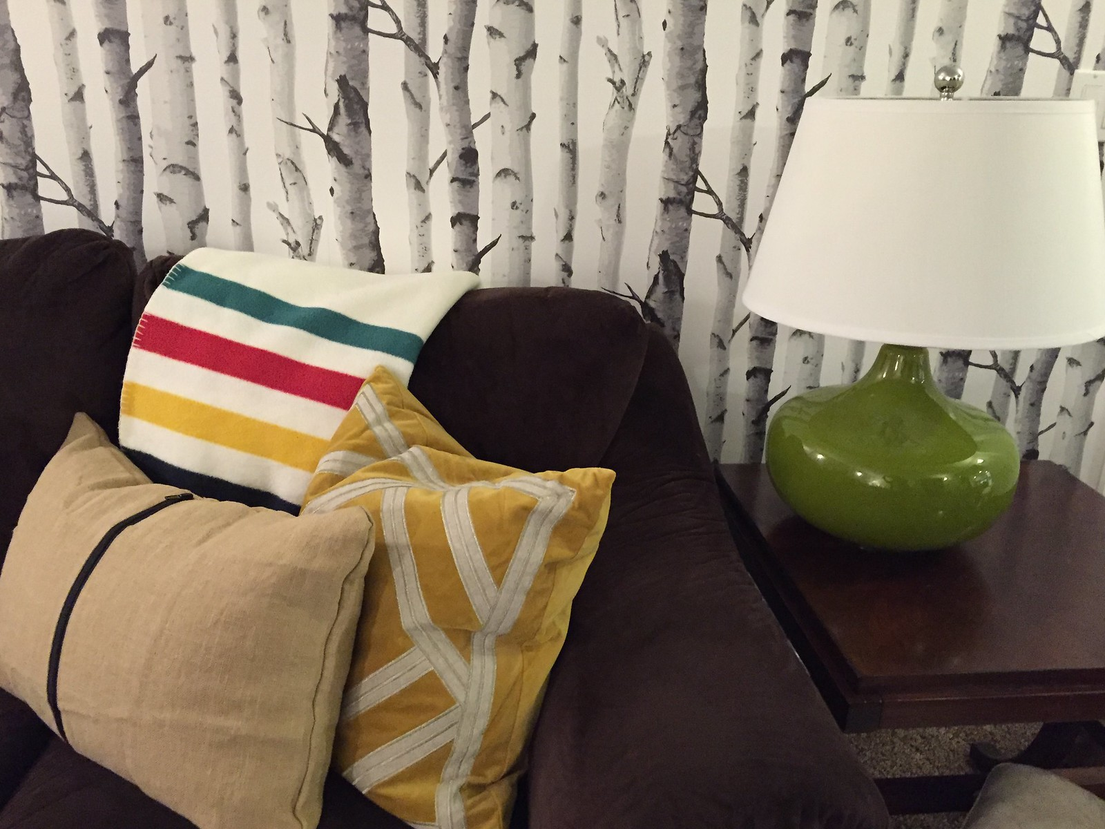 hudson bay blanket on brown sectional with green ceramic lamp on table