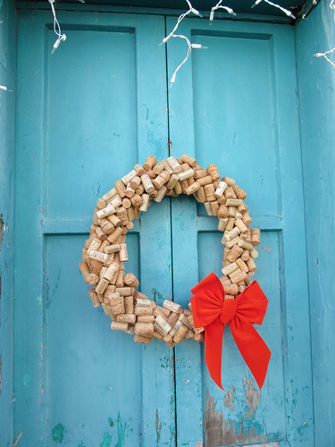 cork wreath with red ribbon on a blue door.