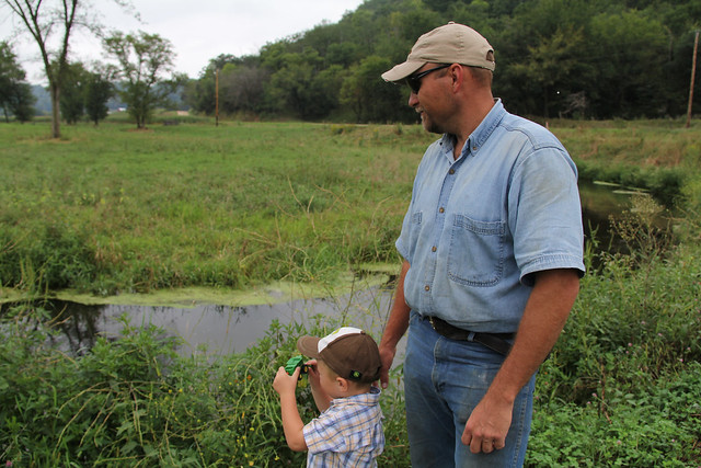 Ryan Pulley and his son look at Pine Creek, which flows through the land where he raises beef cattle in southeastern Minnesota. Photo: Julie MacSwain.