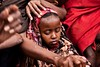 Kenya/Somali refugees.  A mother cradles her baby while putting a hand on her daughter who was doused with water to keep cool under the sweltering sun. New refugees from Somalia wait outside the reception center  in Dagahaley camp. Upon arrival new refuge by ( Voice Nature. )