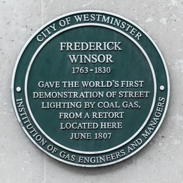 Frederick Winsor green plaque - Frederick Winsor  1763-1830  gave the world's first  demonstration of street  lighting by coal gas,  from a retort  located here  June 1807