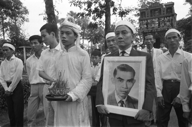 1966-12 - Tran van Van's funeral. Van's brother in law holds portrait of Van - by Francois Sully