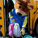 Baxter the Bear of Del Norte Credit Union holds two backpacks in front of Gus the Bus.