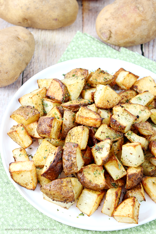 Oven Roasted Potatoes cooked on a plate with potatoes lying next to it.