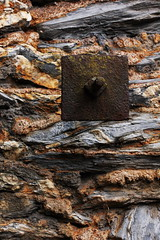 Rusted Metal Square on  a Stone Wall